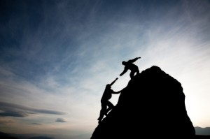 Giving A Hand To Someone Climbing Up A Mountain